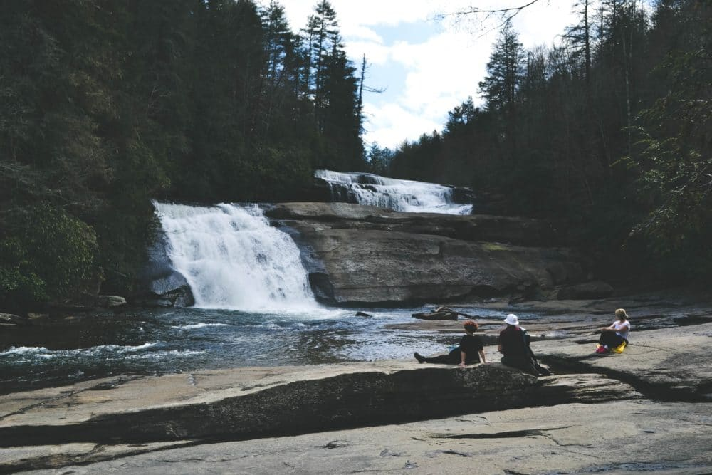 Three people sitting on a grey surface in front of a waterfall photo.