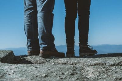 Two persons wearing jeans and hiking boots on a rock ledge.