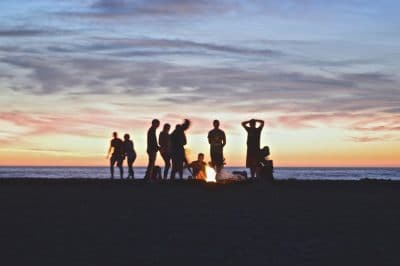 A group of people around a campfire on the beach.