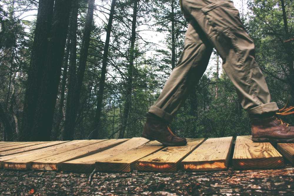 Person walking on brown wooden boards in the woods.