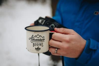A man holding a coffee mug outside in the snow.