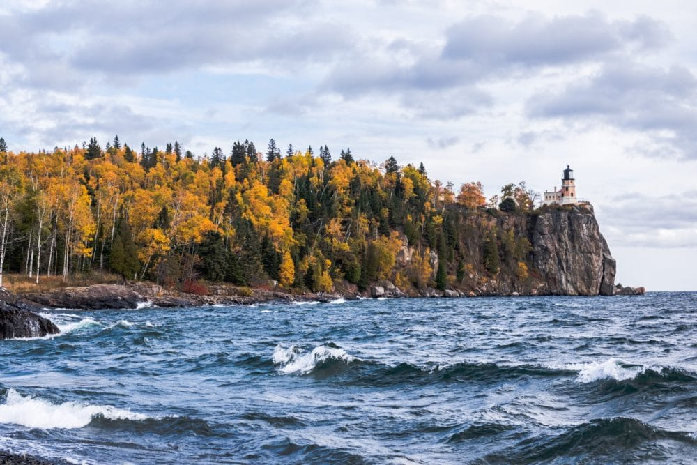 Body of water near island with trees and lighthouse photo.