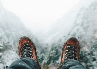 A person wearing boots in the snow outdoors.