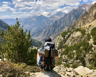 A guy with a hiking backpack on a mountain.