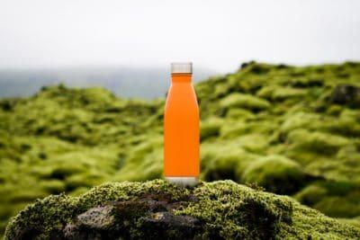 An orange bottle of water outside.