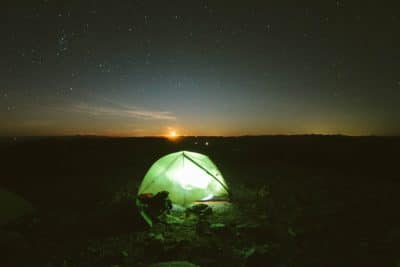 A tent lit up at night.