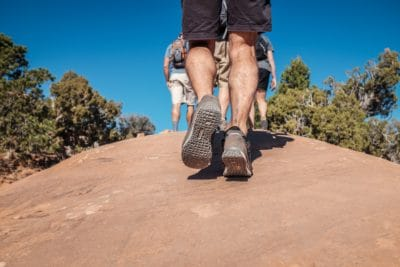 People wearing hiking shoes outdoors.