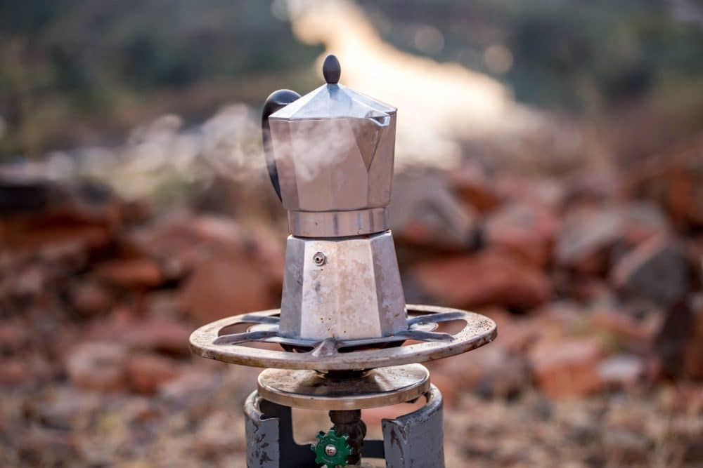A moka pot on a camping stove.