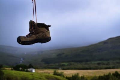 A pair of hiking boots hanging and a green field.