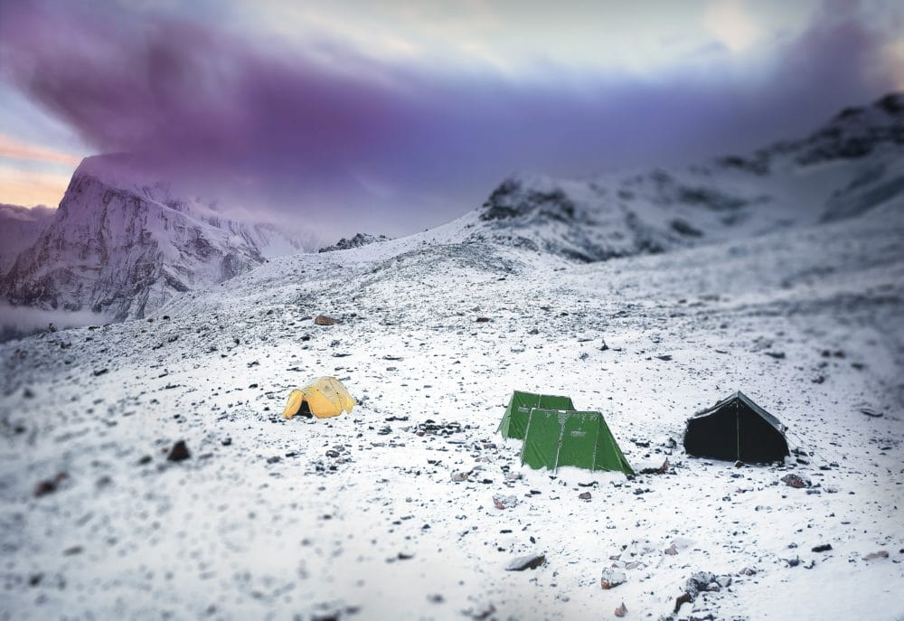 Three tents in the snow, in the mountains of Nepal.