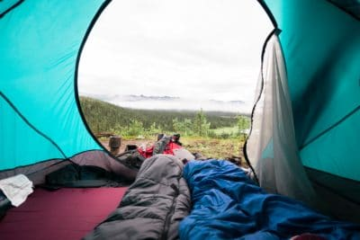 A person in a tent with a sleeping bag.