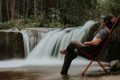 A man sitting in a camping chair by a small waterfall.