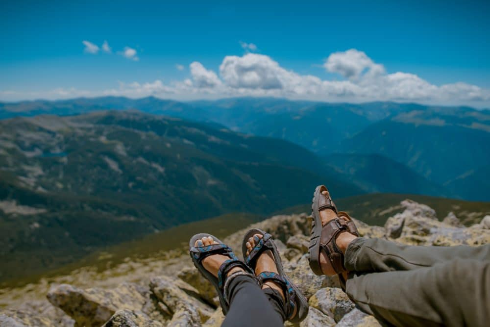 Two pairs of feet on a rock ledge with hiking sandals.