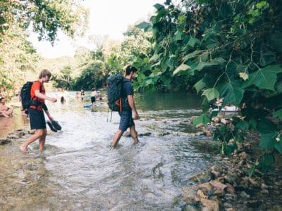 Two men walking across a creek.