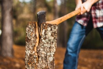Man holding brown axe towards firewood on selective focus photography.