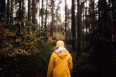 A girl in yellow walking through the forest.