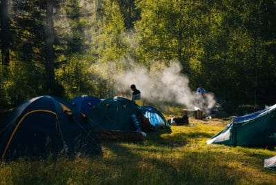 A person near some tents and smoke with trees.