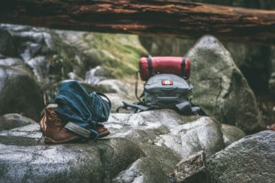 Two hiking backpacks in a creek bed.