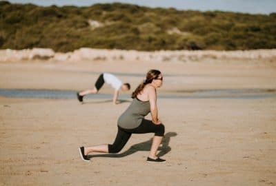 A women doing lunges in brown dirt.