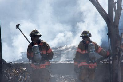 Two firefighters putting out a fire.