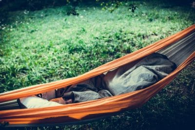 Person lying in an orange hammock outdoors.