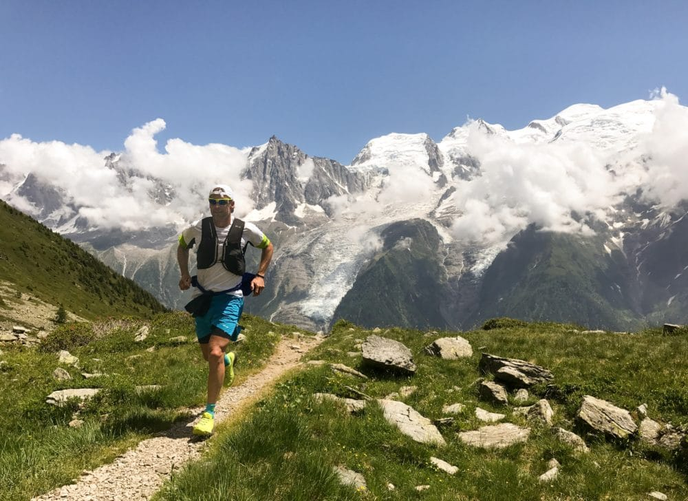 Man in a white shirt running on the ground in the mountains during the daytime.