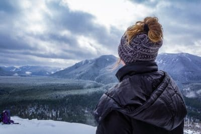 Person standing on a mountain top looking over mountains in the snow.