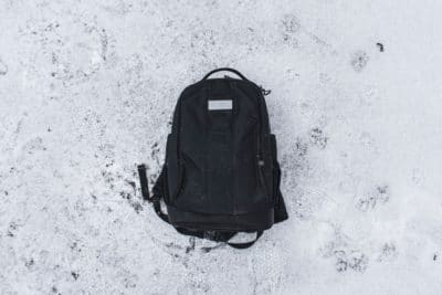 A black hiking daypack in the snow.