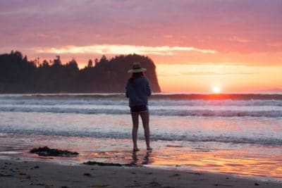 Woman with a camping hat on the beach during sunset.