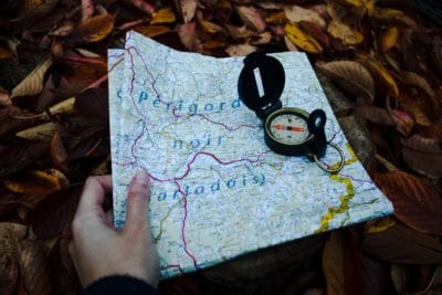 A person holding a map with a compass.