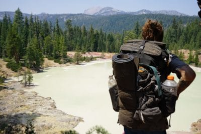Man carrying a black backpack and sleeping pad in the mountains.