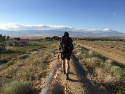 Woman walking on a dirt path in a field.