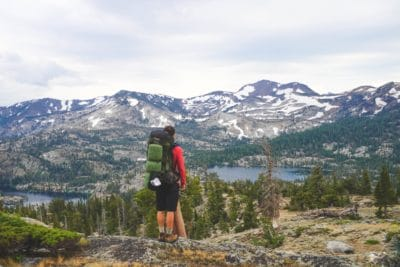 Person standing on a mountain wearing a backpack.