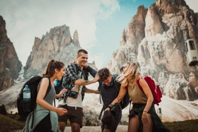 A group of backpackers laughing in the mountains.