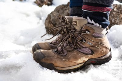 A pair of brown hiking boots in the snow.