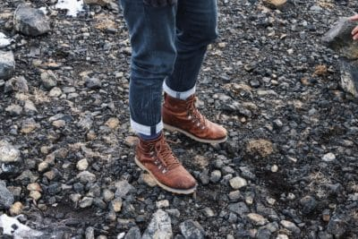 A pair of brown leather boots on rocks.