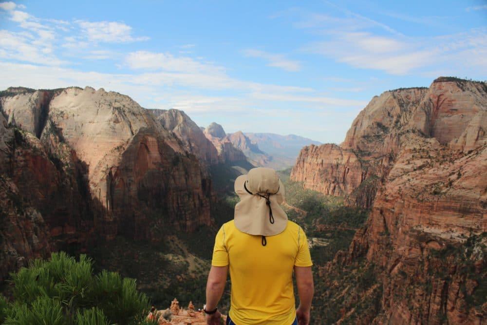 A man wearing a yellow shit and camping hot, looking at a canyon.