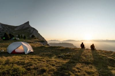 Two people sitting in the mountains by a white tent.