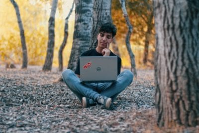 A man with a Dell laptop computer in the forest.
