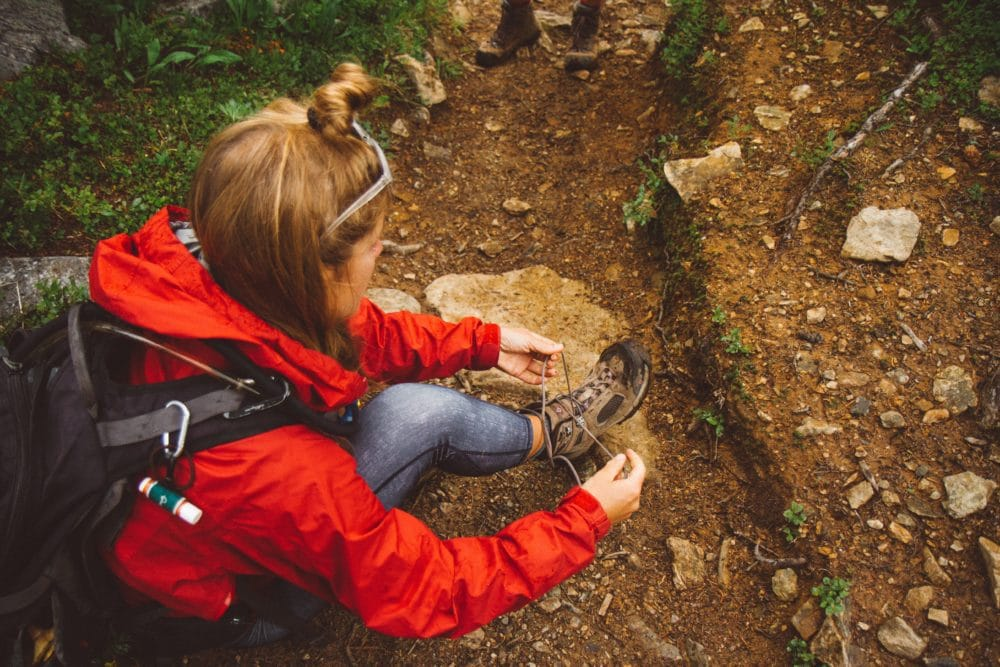 Woman on the ground in a red jacket, tying her hiking boots.