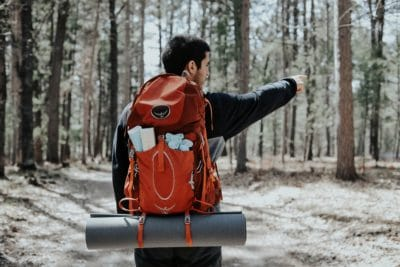 A person in the woods with a red backpack.