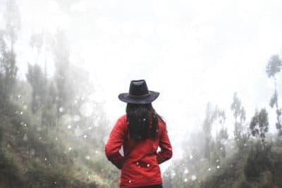 Woman in red coat with a black hat in the snow.
