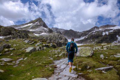Man running near a rocky mountain in the daytime.