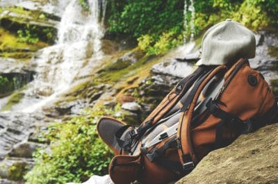 An orange backpack and a hat by a waterfall.
