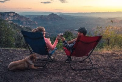 Two person sitting on camping chairs in the mountains.