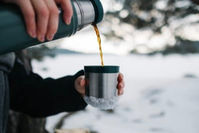 Person pouring coffee into a mug in the snow.