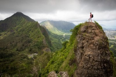 Man on top of a green mountain.