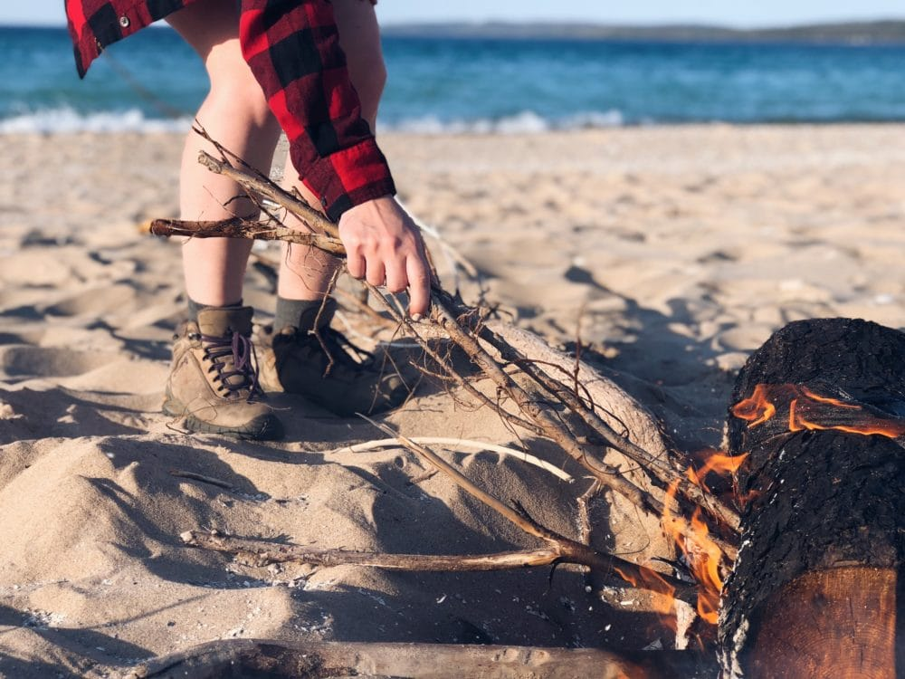 A person making a fire on a beach.