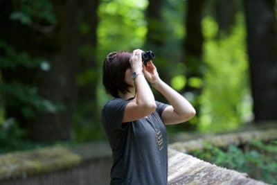 A girl looking through binoculars in the woods.