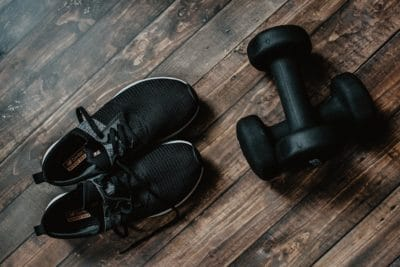 Pair of black running shoes and black dumbbells.